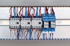 Tre magnetiska contactors och två mellanliggande relär i ett elektriskt kabinett Royaltyfria Foton
