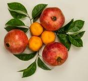 Tre mandarini arancio con tre melograni rossi fotografia stock