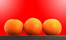 Tre mandarini sparati sopra fondo rosso Fotografia Stock