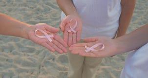 Tre mani che tengono il nastro di consapevolezza del cancro al seno stock footage