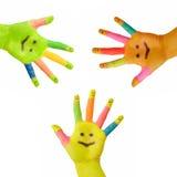 Tre mani variopinte con il sorriso verniciato fotografie stock libere da diritti