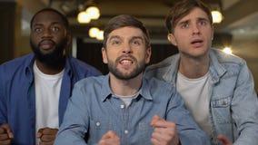 Tre manliga fans som tillsammans känner uppriven modig förlust, hållande ögonen på konkurrens, fritid arkivfilmer