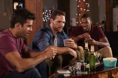 Tre manliga vänner som spelar kort och hemma dricker öl Arkivfoto
