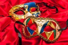 Tre Mardi Gras Masks på rött silke fotografering för bildbyråer