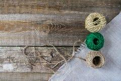 Tre marroni e palla verde del filo con le forbici d'annata antiche sui bordi di legno anziani strutturati Rustico, cucito di sabi Fotografia Stock