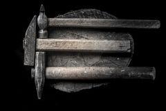 Tre martelli con la maniglia di legno con molte bullette per suole del ferro sul troncone di legno Stile maschio brutale Immagine Stock