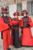 Tre maskerade personer med röda dräkter på den Venedig karnevalet royaltyfri foto
