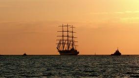 Tre-masted full-riggat högväxt skepp i nästan kust på soluppgång en sommarmorgon turist- skyttelflöten för kontur i hamn stock video