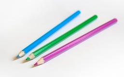 Tre matite di colore su priorità bassa bianca Fotografie Stock