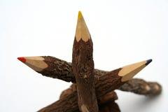 Tre matite fatte di un albero naturale su un cono piny Immagini Stock Libere da Diritti