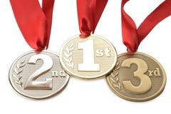 Tre medaljer på vit Arkivfoton