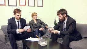 Tre medarbetare som i regeringsställning diskuterar affärsplan lager videofilmer
