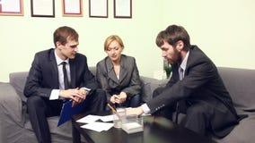 Tre medarbetare som i regeringsställning diskuterar affärsplan stock video