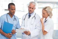 Tre medici che per mezzo di una compressa Immagine Stock