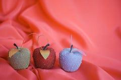 Tre mele dell'albero di Natale su colore rosso immagine stock libera da diritti