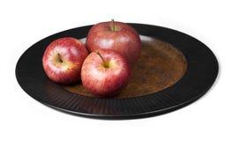 Tre mele rosse su una zolla. Fotografia Stock