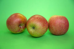 Tre mele su un fondo verde Fotografie Stock