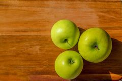 Tre mele sul bordo di legno Immagine Stock