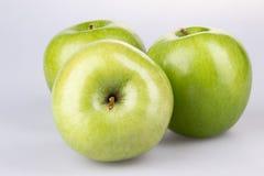 Tre mele verdi su priorità bassa bianca fotografia stock libera da diritti