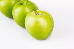 Tre mele verdi sul bianco fotografia stock