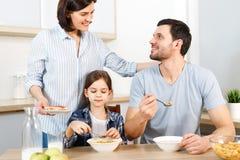 Tre membri della famiglia hanno prima colazione sana deliziosa alla cucina, mangiano i fiocchi di granturco con latte, godono del immagini stock libere da diritti
