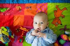 Tre mesi felici del neonato, giocante a casa su una a variopinta Immagine Stock