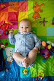 Tre mesi felici del neonato, giocante a casa su una a variopinta Immagini Stock