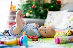 Tre mesi felici del neonato, giocante a casa su una a variopinta Fotografie Stock