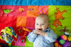 Tre mesi felici del neonato, giocante a casa su una a variopinta Fotografia Stock