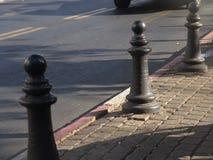 Tre metallstolpar på en stenlagd stads- sikt för trottoar i dagsljus royaltyfri fotografi
