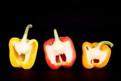 Tre mezzi peperoni domestici su fondo nero puro Pepe domestico della cucina Fotografia Stock