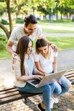 Tre migliori amici in parco che godono del giorno e che per mezzo del computer portatile per Immagine Stock