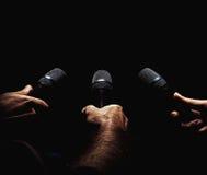 Tre mikrofoner i händer Royaltyfri Foto