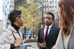 Tre millennial affärskollegor som står på gatan som talar, låg vinkel, slut upp royaltyfri foto