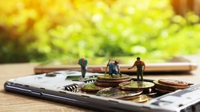 Tre mini figure miniatura con tengono i soldi in cellulare Cashles Immagine Stock