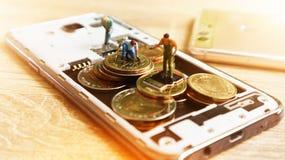 Tre mini figure miniatura con tengono i soldi in cellulare Cashles Fotografia Stock