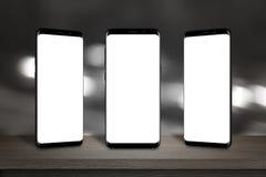 Tre mobiltelefoner med skärmen för modell på tabellen royaltyfri fotografi