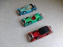 Tre modeller av mång--färgad gammal bil på en grå bakgrund Royaltyfri Bild
