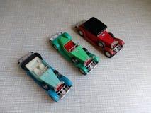 Tre modelli di di vecchia automobile colorata multi su un fondo grigio Fotografia Stock