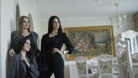 Tre modelli ricchi che posano nella marca copre in appartamento luxurous archivi video