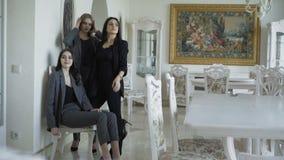 Tre modelli ricchi che posano nella marca copre in appartamento luxurous stock footage