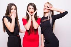 Tre modemodeller i nattklänningar har gyckel på kamera Fotografering för Bildbyråer