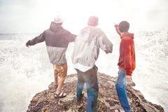 Tre modiga män som står på en klippa royaltyfria bilder