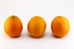 Tre mogna apelsiner på vit bakgrund Fotografering för Bildbyråer