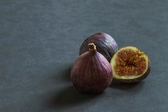 Tre mogna fikonträdfrukter på en grå bakgrund royaltyfria bilder