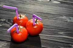 Tre mogna röda tomater med sugrör i dem Royaltyfri Fotografi