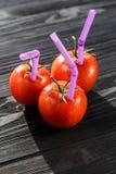 Tre mogna röda tomater med sugrör i dem Arkivbild