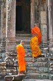 Tre monaci che camminano nel tempio fotografia stock