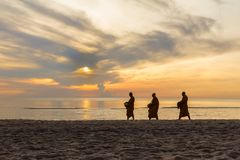 Tre monaci stanno camminando sulla spiaggia Immagine Stock