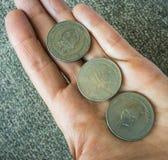 Tre monete tunisine sul woman& x27; palma di s Immagini Stock